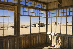 Abandoned houses in desert. View of abandoned and derelict houses in deserted town with encroaching desert Stock Image
