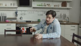Man drinking alcohol with grief in domestic kitchen. Abandoned husband drinking alcohol beverage in despair while sitting at kitchen table alone after breakup stock footage
