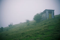 Abandoned hut on foggy hill Royalty Free Stock Photos