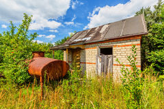 Abandoned hut. Among trees and bushes in summertime Stock Photos