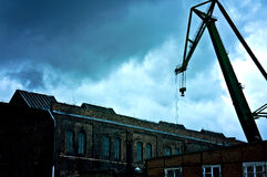Abandoned industrial area. Dark and sullen clouds over old abandoned industrial area with cranes vector illustration