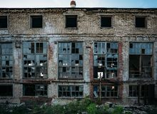 Abandoned industrial building facade, broken windows, shabby walls.  royalty free stock images
