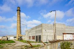 Abandoned industrial building with a high brick chimney. Against a blue sky, fence with barbed wire royalty free stock images