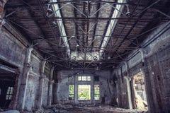 Abandoned industrial creepy warehouse inside with big broken window, old dark grunge factory building. Abandoned industrial creepy warehouse ine with big broken stock image