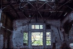 Abandoned industrial creepy warehouse inside with big broken window, old dark grunge factory building. Toned stock images