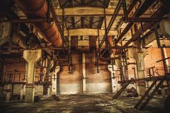 Abandoned industrial creepy warehouse inside old dark grunge factory building. Toned Royalty Free Stock Photography