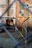 Abandoned industrial entryway. Entryway to abandoned manufacturing structure through fence Royalty Free Stock Photography