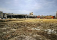 Abandoned industrial facilities and leveled land. Abandoned industrial facilities from former factory in the background and leveled land in foreground prepared royalty free stock photos