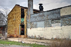 Abandoned Industrial Factory Warehouse Exterior. High dynamic range image of exterior of abandoned warehouse with destroyed metal and brick walls stock photo
