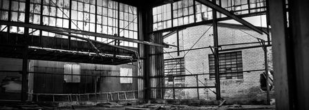 Abandoned Industrial Factory Warehouse Interior. Black and white image of interior of abandoned warehouse with broken glass and destroyed brick walls stock images