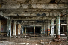 Abandoned Industrial Factory Warehouse Interior. Image of interior of abandoned warehouse with peeling paint, broken glass, destroyed concrete walls, exposed royalty free stock photo