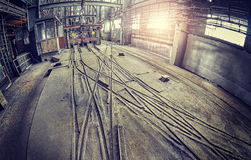Abandoned industrial hall interior with trolley tracks. Royalty Free Stock Images