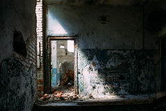 Abandoned industrial interior building, door in bright light and shadow. Toned Royalty Free Stock Photos