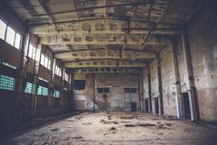 Abandoned industrial warehouse on ruined brick factory, creepy interior, perspective. Toned royalty free stock photos