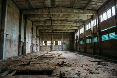 Abandoned industrial warehouse on ruined brick factory, creepy interior, perspective. Toned Royalty Free Stock Images