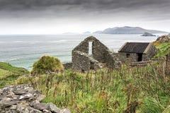 Abandoned Irish Famine Farmhouse on Cliff. Ruins of an old farm abandoned during the Irish Famine on Slea Head Drive, Dingle Peninsula, Ireland Royalty Free Stock Image