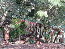 Abandoned iron bridge in the middle of the woods. Abandoned rusty iron bridge, in the middle of a forest, in sunny day Stock Images