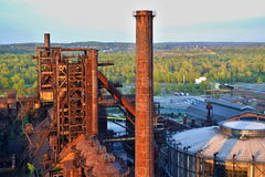 Abandoned ironworks factory - rusty chimney sunlit by the sun