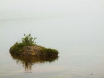 Abandoned island in lake. Big stone si sticking out from cold level.  Royalty Free Stock Photo