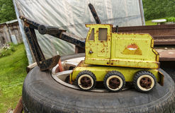Abandoned kids toys. Loader on a pile of old tire in a yard royalty free illustration