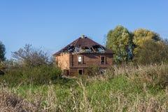Abandoned kollapsande tegelstenhus bland täta busksnår royaltyfri bild