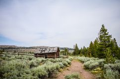 Abandoned log cabin with a dirt trail in Miners Delight Wyoming, a former mining town and camp, now a ghost town. In summer royalty free stock photography