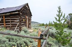 Abandoned log cabin with a dirt trail in Miners Delight Wyoming, a former mining town and camp, now a ghost town. In WY royalty free stock photo