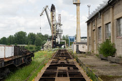 Abandoned looking industrial shipyard with large crane and railtracks Stock Photo