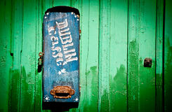 Abandoned mail box. Old abandoned mail box with sign DUBLIN CAFFE on green fence Stock Photo