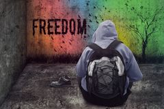 Abandoned man drawing freedom on the wall in a closed grunge room Stock Photos