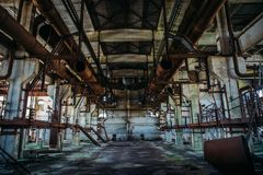 Abandoned metallurgical factory or warehouse left by people after war. Toned stock photo
