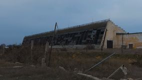 Abandoned Military hangars. And buildings in a closed area with barbed wire. Technical territory with technical objects. The camera moves slowly along the stock footage