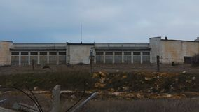 Abandoned Military hangars. And buildings in a closed area with barbed wire. Technical territory with technical objects. The camera moves slowly along the stock video footage