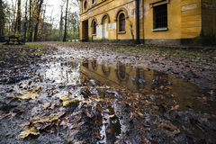 Abandoned mill reflected in a puddle. A yellow old abandoned mill reflected in a puddle - Park of Monza, Italy royalty free stock image