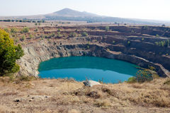 Abandoned mine. Abandoned open ore mine pit partially full of water royalty free stock photography