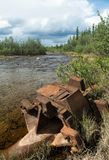 Abandoned mining equipment rusting along fast flowing Alaskan st royalty free stock photo