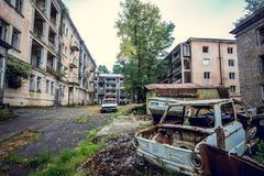 Abandoned mining ghost-town Jantuha, Abkhazia. Destroyed empty houses. The remains of the cars, remnant of The Georgian-Abkhazian war Royalty Free Stock Photo