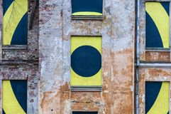 Abandoned monument facade with a yellow round target sign behind the windows. Abandoned monument with a warning sign in the windows Royalty Free Stock Photo