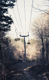 Empty Mountain Chairlift in the forest with wood chairs royalty free stock photo
