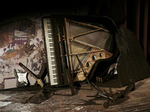Abandoned music. Broken electric guitar and piano resting on a dirty floor and a wall with torn posters Royalty Free Stock Photos
