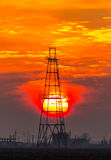 Abandoned oil and gas rig profiled on dramatic evening sky Stock Images