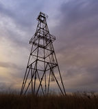 Abandoned oil and gas rig. Profiled on sky Stock Image