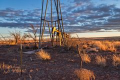 Oil Well Pump. And drilling rig in an abandoned oil field on the plains royalty free stock photography