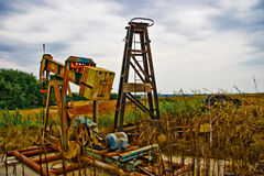 Abandoned Oil Pump. Becuse of the drying up of an oil field this oil pump sets abandoned beside an Oklahoma wheat field Royalty Free Stock Photo