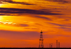 Abandoned oil rig, power lines and sunset Stock Photo