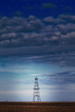 Abandoned oil rig profiled on cloudy day sky Stock Photos