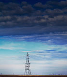 Abandoned oil rig profiled on cloudy day sky Stock Image