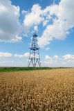 Abandoned oil well. And barley field Royalty Free Stock Images