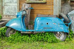 Old soviet moped next to a country house. Abandoned old blue soviet moped laid next to a country house Royalty Free Stock Photos