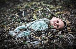 Abandoned old broken baby doll rots in scary forest. Fear and dead Stock Photography